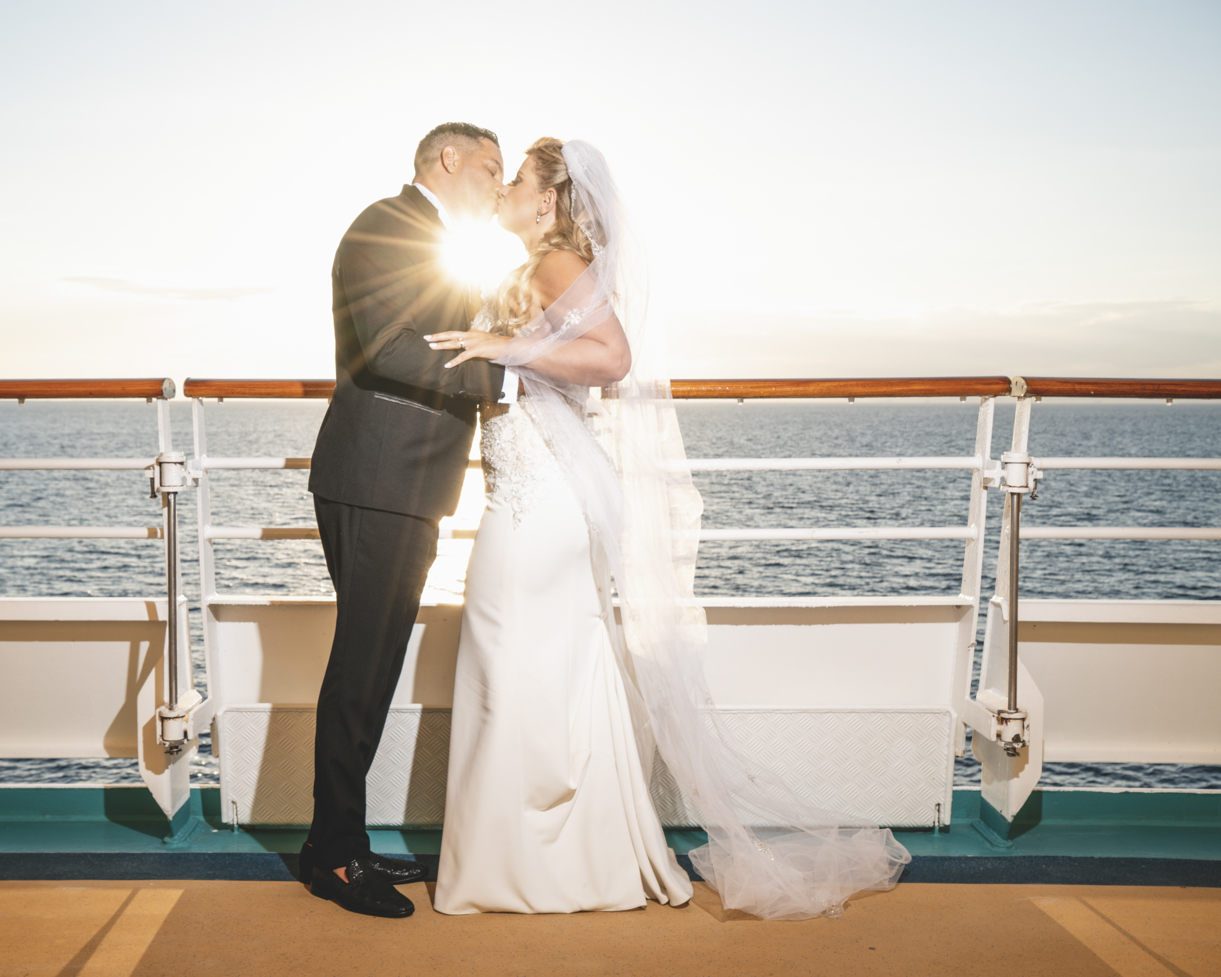Bride & groom kissing with sunburst