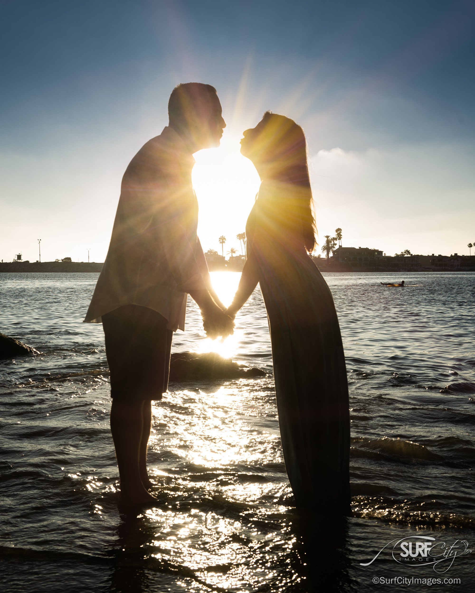 Newly engaged couple in silhouette with sunburst